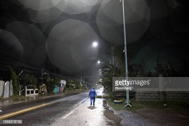 A man dressed in a raincoat walks on an empty street ahead of Typhoon Mangkhut's arrival in Tuguegarao Cagayan province the Philippines on Friday...