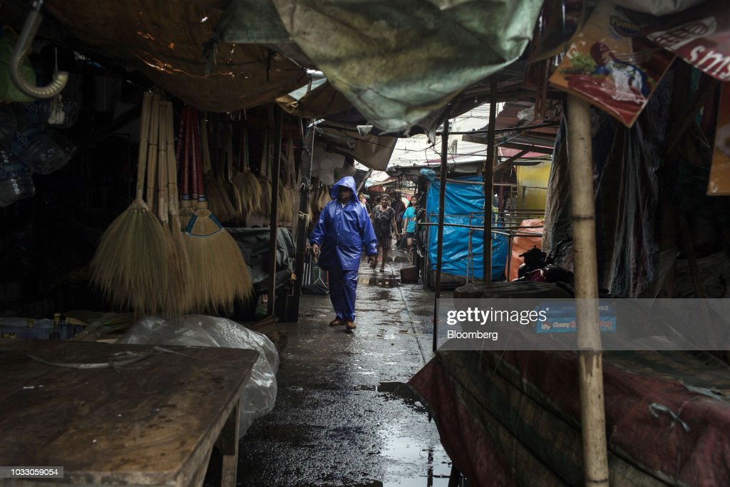 A man dressed in a raincoat walks through a closed market ahead of Typhoon Mangkhut's arrival in Tuguegarao, Cagayan province, the Philippines, on Friday, Sept. 14, 2018. Philippines authorities are evacuating thousands of people in the path of Super Typhoon Mangkhut to safer grounds hours before the cyclone slams into the countrys northern provinces. Photographer: Carlo Gabuco/Bloomberg via Getty Images