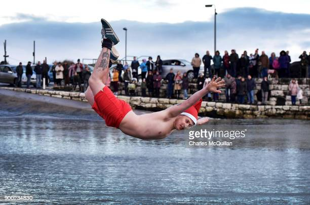 A man dressed in a Santa hat braves the wintry conditions as swimmers take part in the annual New Years Day swim at Carnlough harbour on January 1...