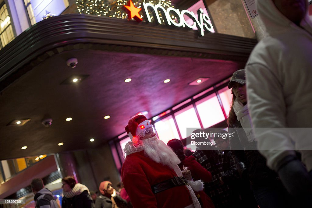 A man dressed in a Santa suit stands on the sidewalk outside Macy's Inc. department store as holiday shoppers enter and leave the department store in New York, U.S., on Sunday, Dec. 23, 2012. Holiday shoppers descended on U.S. stores this weekend in a last-minute dash to buy gifts amid concerns about the nation's economy and the impasse in Washington over taxes and spending. Photographer: Victor J. Blue/Bloomberg via Getty Images