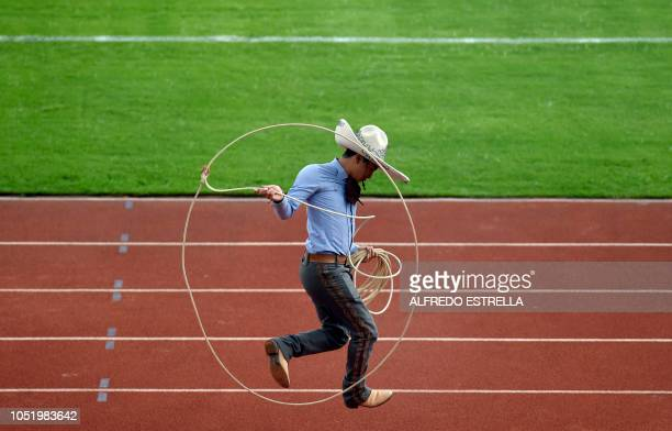 TOPSHOT A man dressed in a tradition 'Charro' costume performs during the ceremony to mark the 50th anniversary of Mexico's 1968 Summer Olympics at...