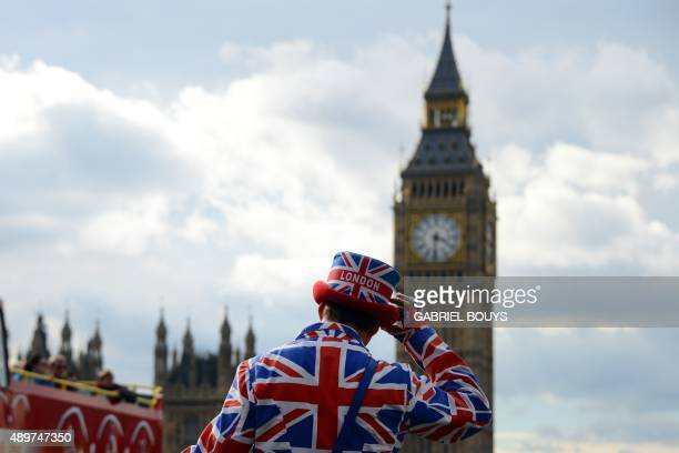 A man dressed in a Union Flagthemed hat and coat acknowledges tourists as they pass Big Ben and the Houses of Parliament in central London on...