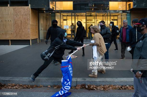 A man dressed in black tries to take a Trump 2020 flag from an elderly Trump supporter near Black Lives Matter in Washington DC on November 14 2020