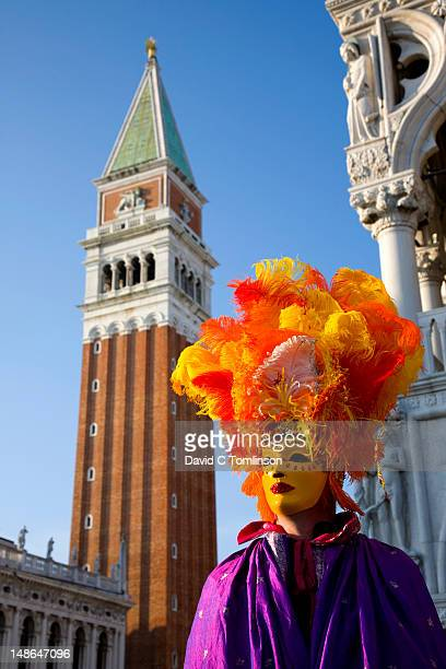 Man dressed in carnival costume and mask posing in front of the Campanile di San Marco during the Venice Carnival, Piazzetta San Marco, San Marco district.