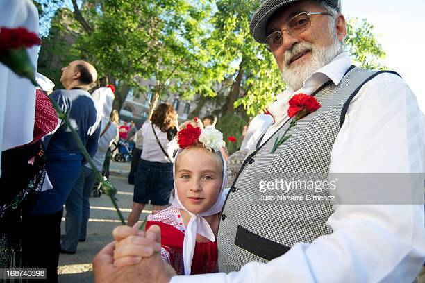 A man dressed in chulapo and young girl look on during the festivities on May 14 2013 in Madrid Spain These festivities are in honor of San Isidro...