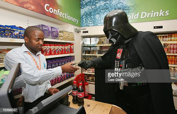 A man dressed in Darth Vader costume buys a drink from a refreshment shop at the Celebration Europe Exhibition in Excel Centre on July 13 2007 in...