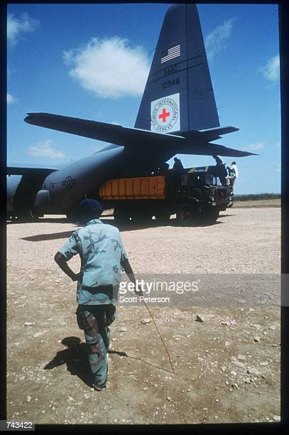 A man dressed in fatigues stands near the tail of a US Air Force plane while the US organized air bridge of food is flown to Somalia August 28 1992...