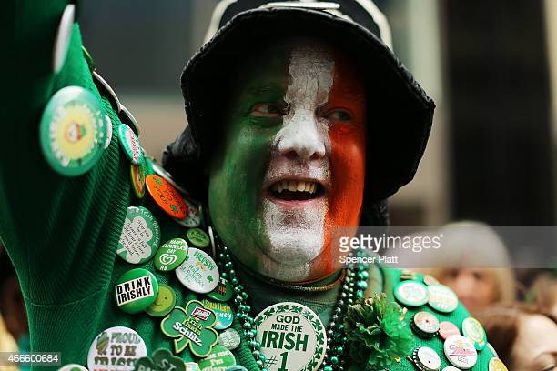 A man dressed in Irish colors cheers the marchers as they make their way up 5th Avenue during New York City's St Patrick's Day Parade on March 17...