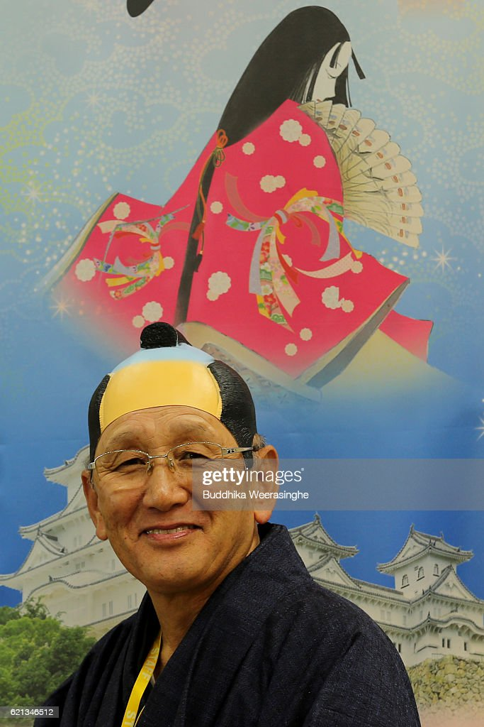 a man dressed in japanese traditional costume stands in front of the advertisement himeji castle poster - Traditional Castle 2016