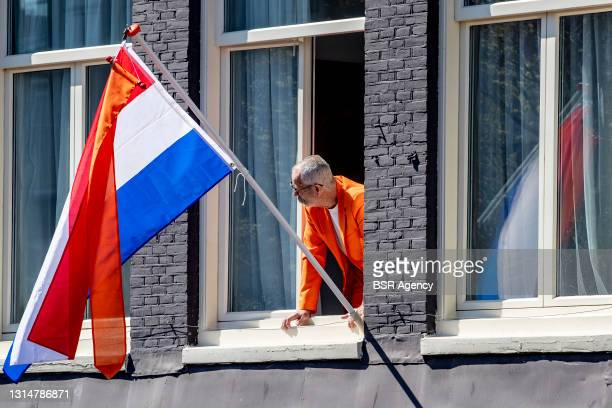 Man dressed in orange clothes looks out a window during King's Day 2021 on April 27, 2021 in Amsterdam, Netherlands. Due to the coronavirus pandemic,...