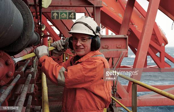 Man Dressed in Orange Working on an Oil Rig