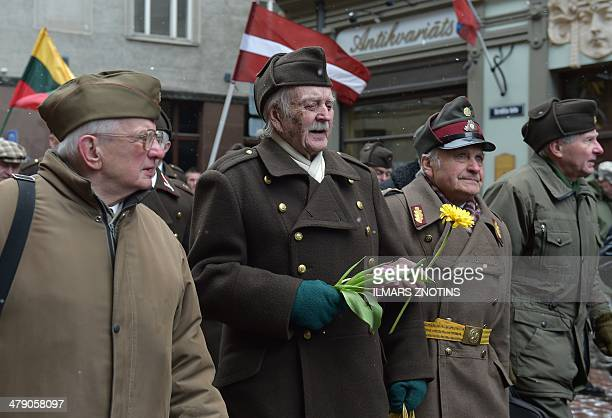 Man dressed in preWWII Latvian military uniforms walk along with veterans of the Latvian Legion a force that was commanded by the German Nazi Waffen...