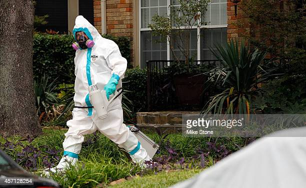 A man dressed in protective hazmat clothing walks towards an apartment where a second person diagnosed with the Ebola virus resides on October 12...
