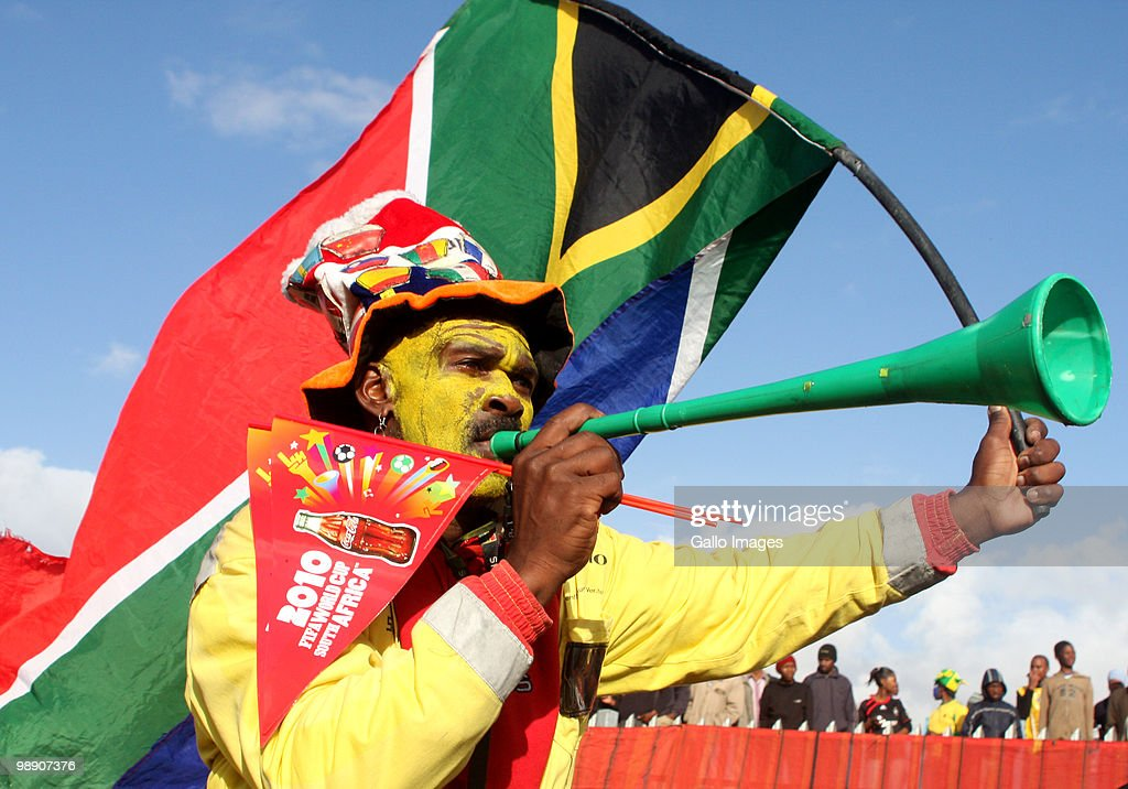 A man dressed in South African football paraphernalia walk past football fans waiting to enter the O.R Tambo center and see the FIFA World Cup trophy after the unveiling, during the kick off of its South African tour in Kayelitsha on May 07, 2010 on the outskirt of Cape Town, South Africa. Football's biggest prize made a 130 000km journey across the world before arriving in the 2010 host country on May 5, 2010. The World Cup will visit 38 towns and cities in South Africa ahead of the tournaments June 11 kick-off.