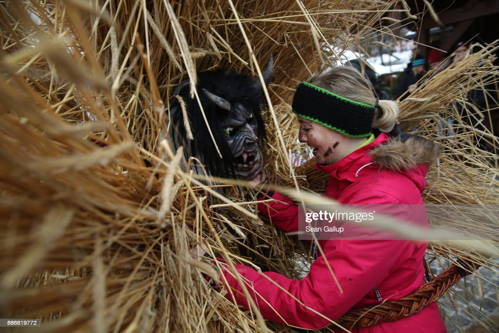 A man dressed in straw and a wooden mask in the form of a figure known locally as 'Buttnmandl', or 'Shaking Man', embraces a female onlooker with a switch made of branches that is meant to ensure fertility in an annual tradition on December 5, 2017 in Berchtesgaden, Germany. Buttnmandl wears heavy cowbells that he rings by shaking his hips. His role is to drive away the evils spirits of winter and awaken slumbering Mother Nature. He also accompanies Saint Nicholas and goes house to house, visiting families as Saint Nicholas hears which children have been good and which have been bad. Buttnmandl is specific to the Berchtesgadener Land region of southeastern Bavaria but is similar in intent to the more common Krampus, the fur-clad figure with a terrifying mask that has, especially in recent decades, become an intrinsic part of local folklore throughout late November and most of December in the alpine regions of Germany, Austria and Italy.