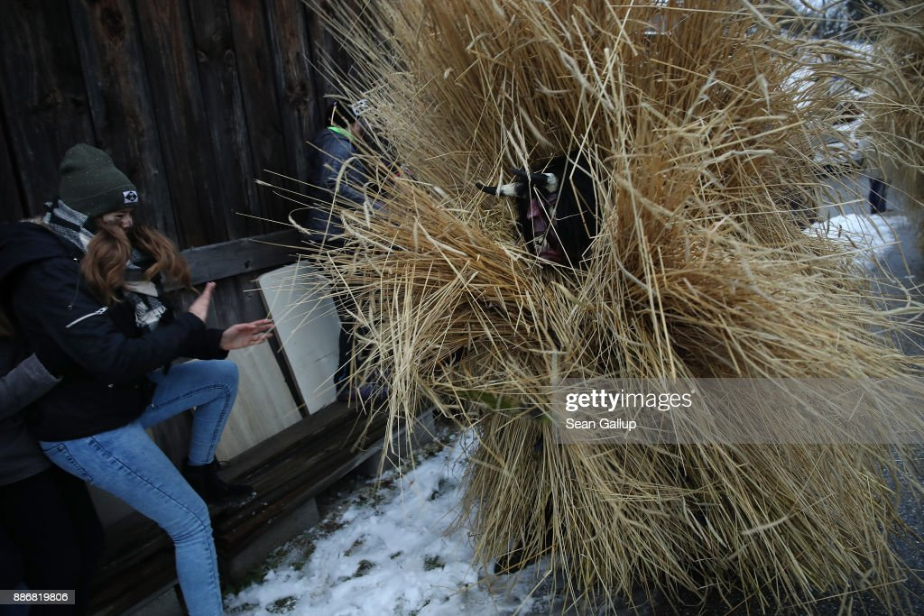 A man dressed in straw and a wooden mask in the form of a figure known locally as 'Buttnmandl', or 'Shaking Man', whips a female onlooker with a switch made of branches that is meant to ensure fertility in an annual tradition on December 5, 2017 in Berchtesgaden, Germany. Buttnmandl wears heavy cowbells that he rings by shaking his hips. His role is to drive away the evils spirits of winter and awaken slumbering Mother Nature. He also accompanies Saint Nicholas and goes house to house, visiting families as Saint Nicholas hears which children have been good and which have been bad. Buttnmandl is specific to the Berchtesgadener Land region of southeastern Bavaria but is similar in intent to the more common Krampus, the fur-clad figure with a terrifying mask that has, especially in recent decades, become an intrinsic part of local folklore throughout late November and most of December in the alpine regions of Germany, Austria and Italy.