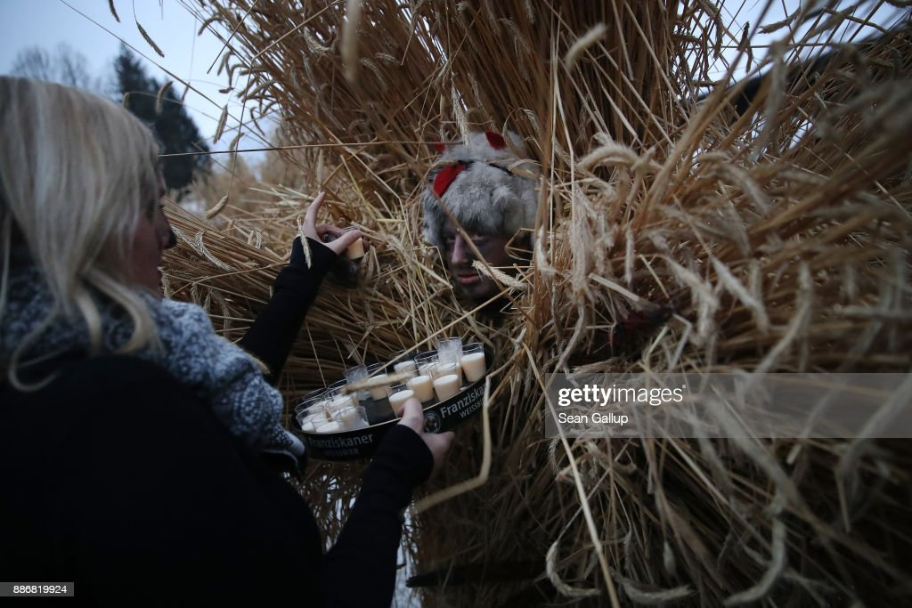 A man dressed in straw and a wooden mask in the form of a figure known locally as 'Buttnmandl', or 'Shaking Man', receives refreshment duiring a break while ha and about a dozen other Buttnmandels paraded house to house in an annual tradition on December 5, 2017 in Berchtesgaden, Germany. Buttnmandl wears heavy cowbells that he rings by shaking his hips. His role is to drive away the evils spirits of winter and awaken slumbering Mother Nature. He also accompanies Saint Nicholas and goes house to house, visiting families as Saint Nicholas hears which children have been good and which have been bad. Buttnmandl is specific to the Berchtesgadener Land region of southeastern Bavaria but is similar in intent to the more common Krampus, the fur-clad figure with a terrifying mask that has, especially in recent decades, become an intrinsic part of local folklore throughout late November and most of December in the alpine regions of Germany, Austria and Italy.
