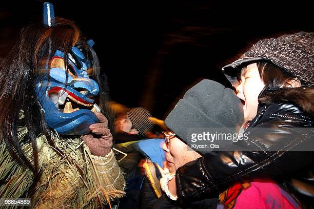 A man dressed in straw clothes and an orge mask as Namahage or a mountain demon scares a child during the Namahage Sedo Festival at Shinzan Shrine on...