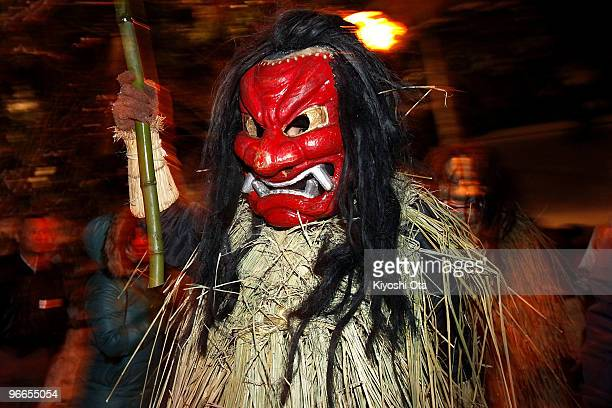 A man dressed in straw clothes and an orge mask as Namahage or a mountain demon marches through the grounds of the shrine during the Namahage Sedo...