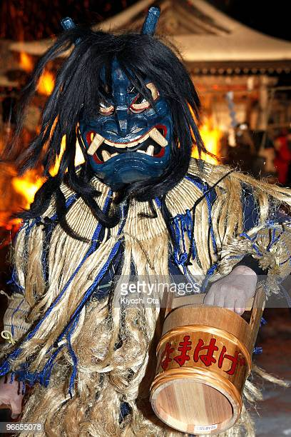 A man dressed in straw clothes and an orge mask as Namahage or a mountain demon performs dances during the Namahage Sedo Festival at Shinzan Shrine...