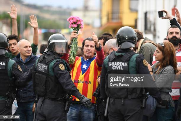 A man dressed in the Catalonian flag holds up pink flowers and gives the thumbs up as police move in on the crowds gathered outside to prevent them...