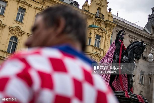 Man dressed in the Croatian national colours walks past the monument of the 19th-century rebel nobleman, Ban Jelacic, covered with Croatian national...