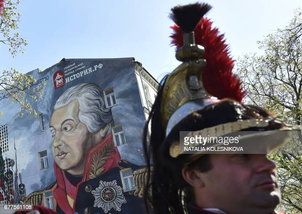 Man dressed in the uniform of the Imperial Russian army attends the opening of a street art-style painting depicting Russian Field Marshal Mikhail...