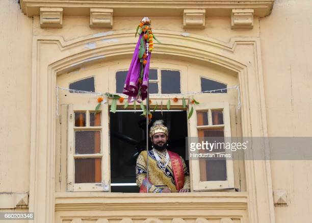 A man dressed in traditional attire watches the procession celebrating 'Gudi Padwa' or the Maharashtrian New Year from his balcony at Girgaum on...