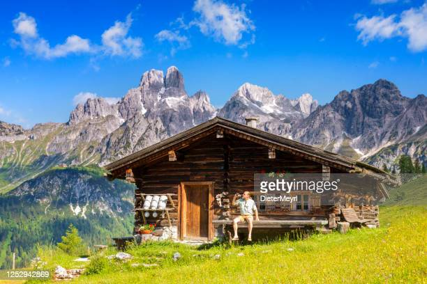 man dressed in traditional austrian or bavarian clothes sitting on bench in front of alpine hut, enjoying beer in alps - austria stock pictures, royalty-free photos & images