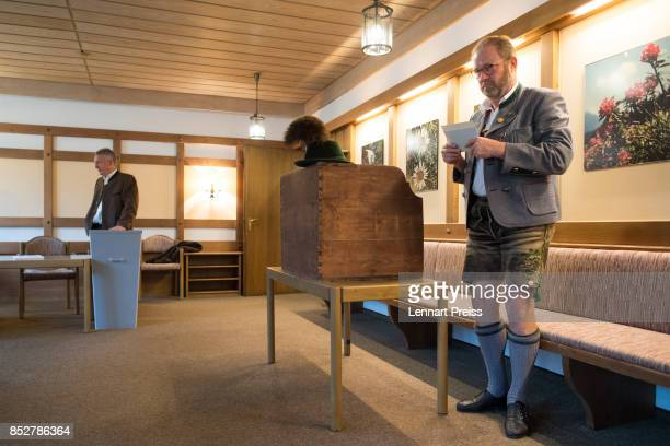 A man dressed in traditional Bavarian clothes stands next to a voting booth at a polling station during German federal elections on September 24 2017...