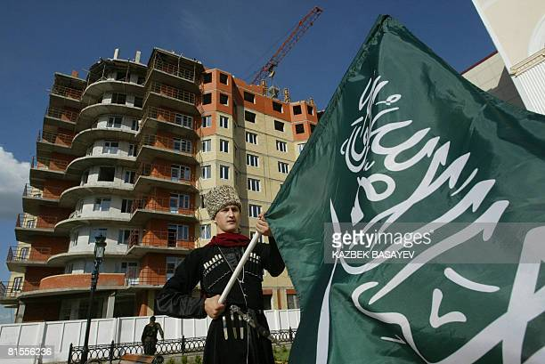 A man dressed in traditional clothing of Russia's Chechnya Republic holds a Saudi Arabian flag during the opening festivities of an international...