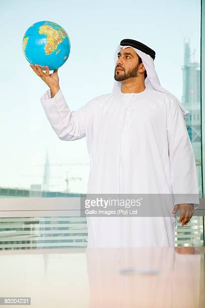 Man dressed in traditional Middle Eastern attire holding globe, Dubai cityscape in background, UAE