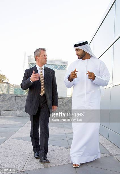 Man dressed in traditional Middle Eastern attire walking and talking with Western businessman, Dubai, UAE