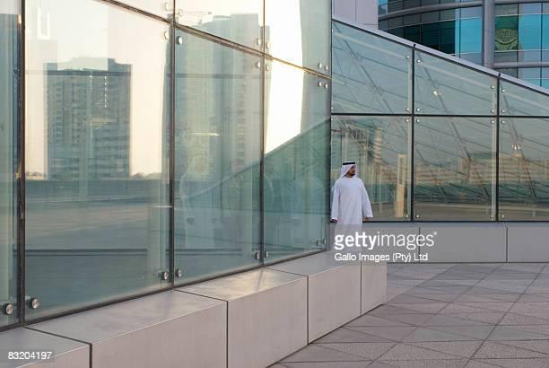 Man dressed in traditional Middle Eastern attire walking through glass building, Dubai, UAE