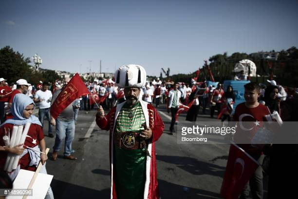 A man dressed in traditional Ottoman costume holds a Turkish national flag during a march on the anniversary of last year's failed coup in Istanbul...
