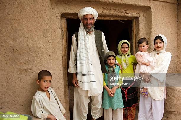A man dressed in traditional outfit stands with his family outside their home in Rabat Mirzaha village 50 kilometers west of Herat province...