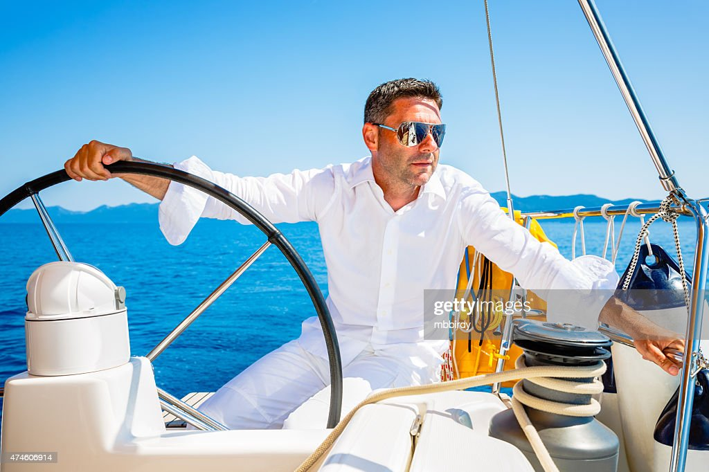 Man dressed in white sailing with sailboat : Stock Photo