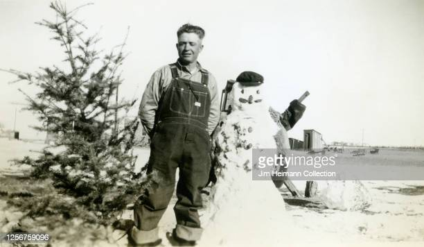 A man dressed like a farmer in denim overalls stands between a Christmas tree and a humorous snowman in a field circa 1943