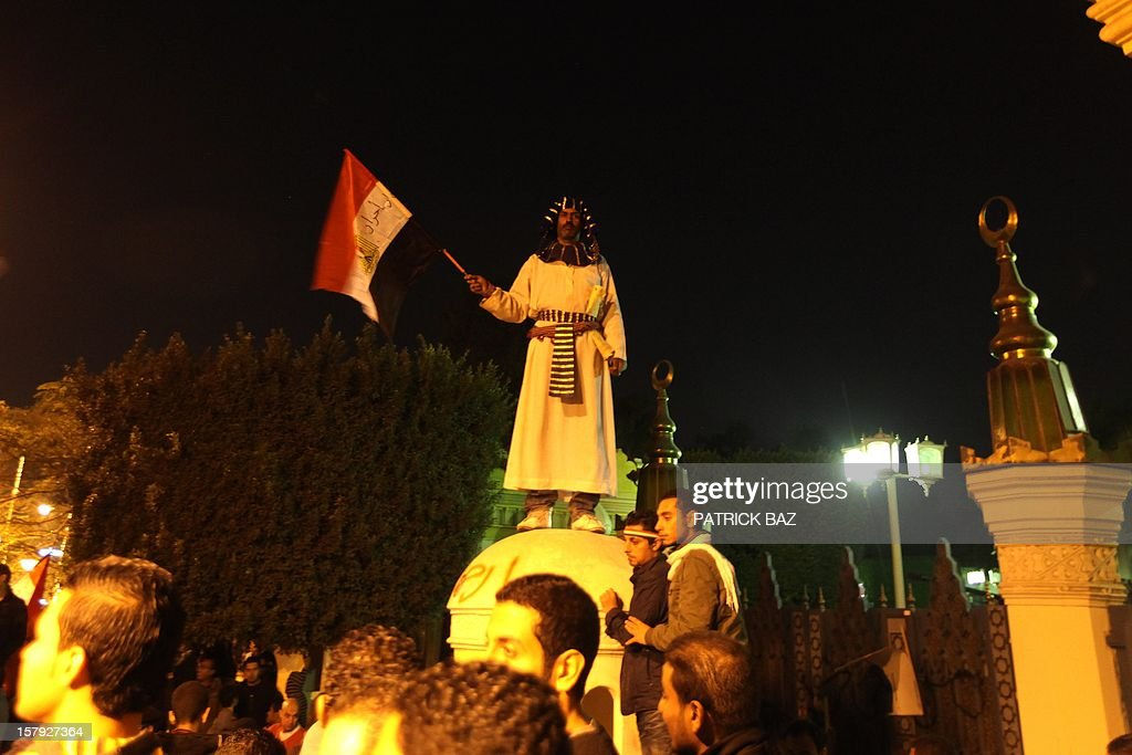 A man dressed like a Pharaoh stands on top of the wall of the Egyptian presisential palace as thousands of protesters against Egyptian president Mohamed Morsi gather in front of the palace on Decem...