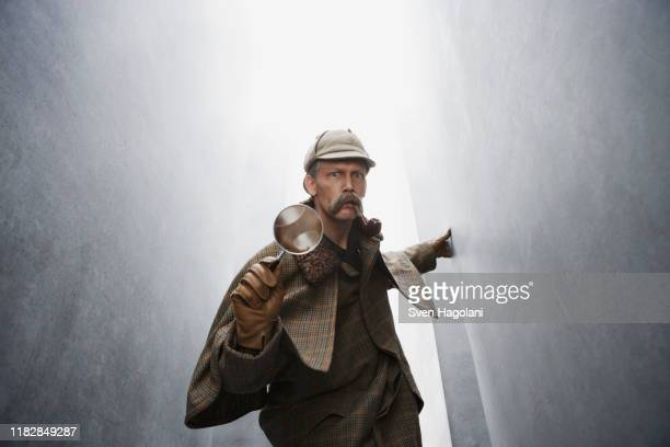 a man dressed like sherlock holmes holding a magnifying glass - sherlock holmes stock pictures, royalty-free photos & images