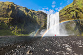 Man dressed standing at the base of Skogafoss waterfall
