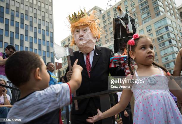 A man dressed to resemble President Donald Trump interacts with children as activists rally against the Trump administration's immigration policies...