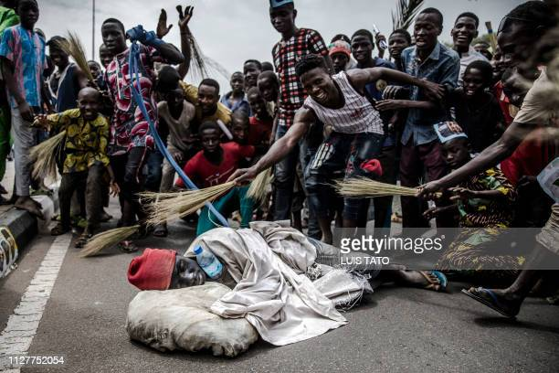 TOPSHOT A man dressed up as a homeless person and other All Progressives Congress party supporters celebrate after the incumbent president's victory...