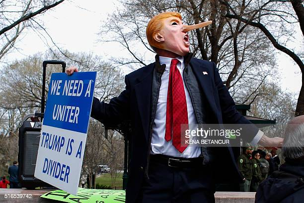A man dressed up as Donald Trump holds a banner during a protest rally against Republican presidential frontrunner Donald Trump in New York on March...