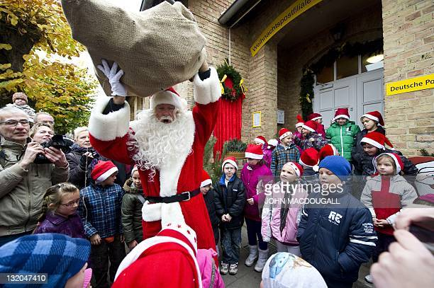 A man dressed up as Santa Claus prepares to give out gifts to local children as he arrives at the Santa Claus post office in the Eastern German town...