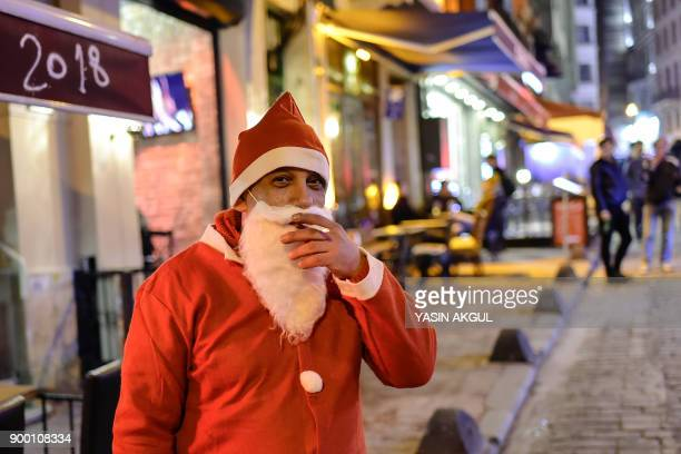 A man dressed up as Santa Clause smokes a cigaret close to Taksim square where Turkish security forces are on patrol as people prepare to celebrate...