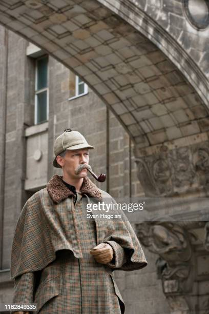a man dressed up as sherlock holmes standing under a building arch looking away - sherlock holmes stock pictures, royalty-free photos & images