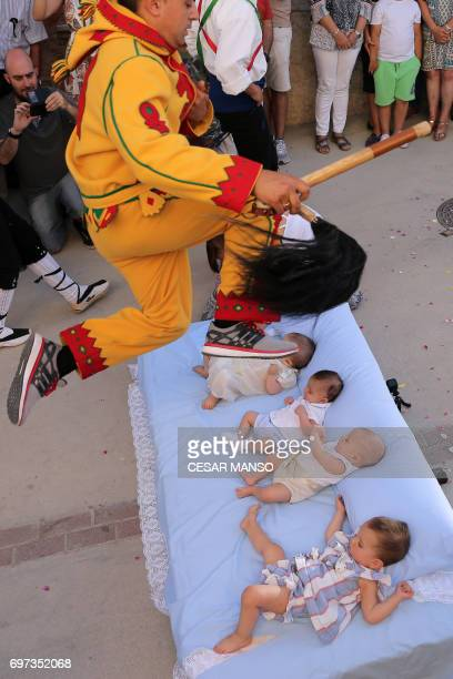 A man dressed up as the devil jumps over babies lying on a mattress in the street during 'El Colacho' the 'baby jumping festival' in the village of...