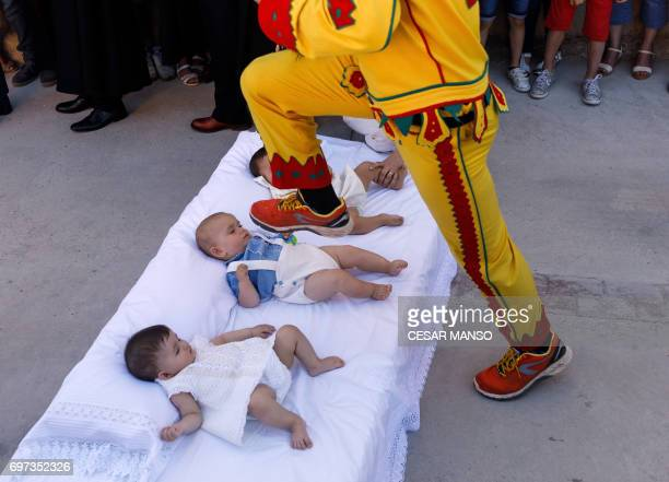 TOPSHOT A man dressed up as the devil jumps over babies lying on a mattress in the street during 'El Colacho' the 'baby jumping festival' in the...