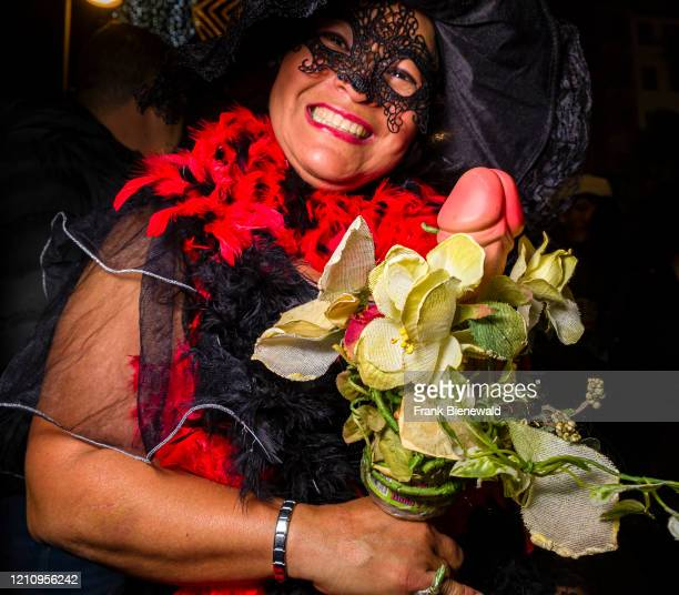A man dressed up in mourning clothes carrying a dildo and smiling partying in the streets during the funeral procession Burial of the Sardine the...